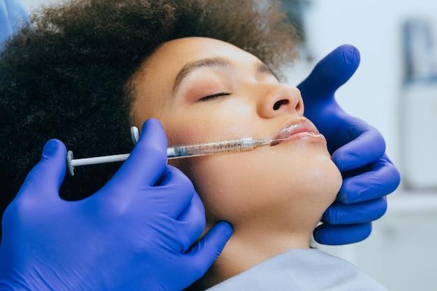 Mulher jovem e atraente africana está recebendo injeções faciais rejuvenescedoras. ela está calmamente sentada na clínica.