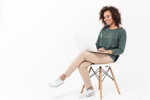 Mulher jovem e atraente africana sentada em uma cadeira isolada sobre uma parede branca, usando um laptop