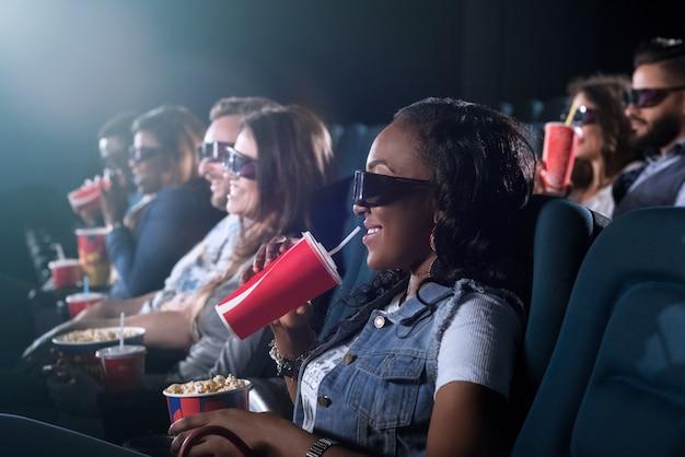 Mulher jovem e atraente africana sorrindo alegremente segurando sua coca-cola e pipoca assistindo a um filme no cinema