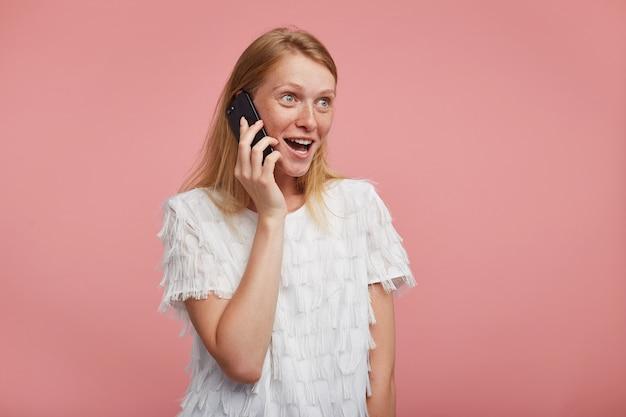 Mulher jovem e atraente agitada com maquiagem natural, olhando alegremente para a frente com rosto animado enquanto faz uma ligação para a amiga, em pé contra um fundo rosa