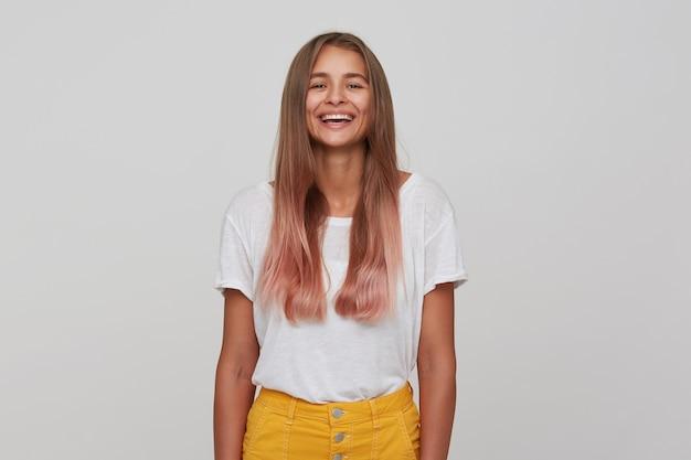 Mulher jovem e atraente, alegre, com cabelo comprido castanho claro, rindo alegremente enquanto olha, estando em alto astral enquanto fica em pé sobre uma parede branca com roupa casual
