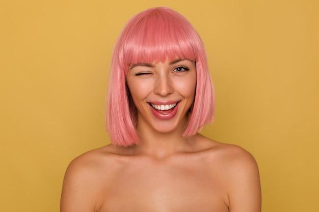 Mulher jovem e atraente alegre com cabelo curto rosa, mantendo um olho fechado enquanto olha alegremente para a câmera, estando de bom humor e sorrindo amplamente, isolada sobre uma parede de mostarda