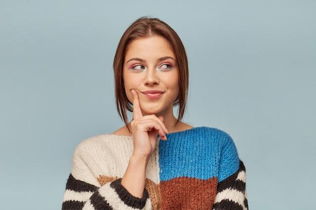Mulher jovem e atraente alegre com maquiagem brilhante segura um dedo perto da bochecha e olha pensativamente para longe