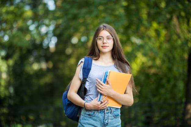 Mulher jovem e atraente alegre com mochila e notebooks em pé e sorrindo no parque
