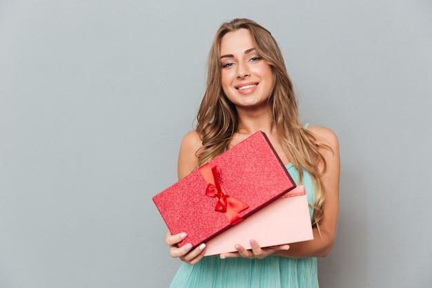 Mulher jovem e atraente alegre em pé e abrindo a caixa de presente na parede cinza