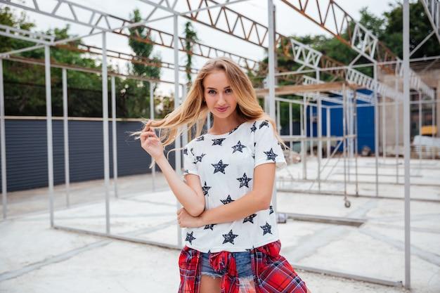 Mulher jovem e atraente alegre posando ao ar livre