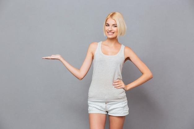 Mulher jovem e atraente alegre segurando copyspace na palma da mão sobre uma parede cinza