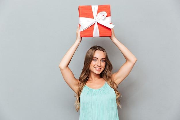 Mulher jovem e atraente alegre segurando uma caixa de presente acima da cabeça