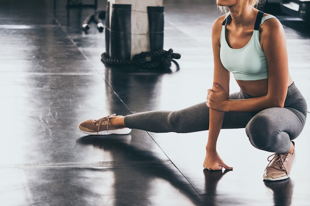 Mulher jovem e atraente alongamento e aquecimento antes de treino no ginásio