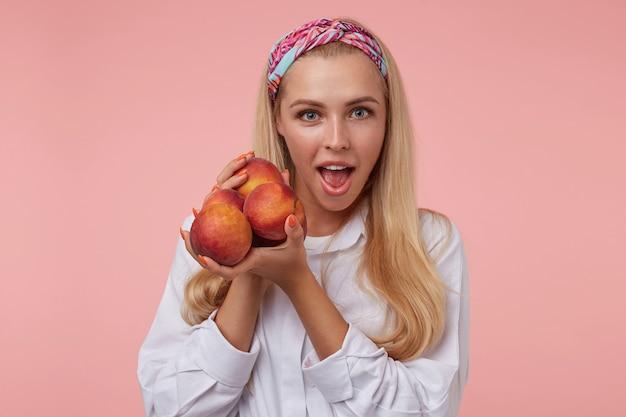 Mulher jovem e atraente animada com pêssegos nas mãos, olhando com a boca bem aberta, usando uma faixa colorida e camisa branca, isolada
