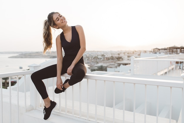 Mulher jovem e atraente animada no sportswear, apreciando o nascer do sol na beira-mar da manhã em um país tropical. humor alegre, emoções verdadeiras, estilo de vida saudável, sorrindo com os olhos fechados