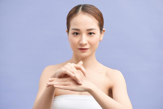 Mulher jovem e atraente aplicando creme para as mãos na violeta
