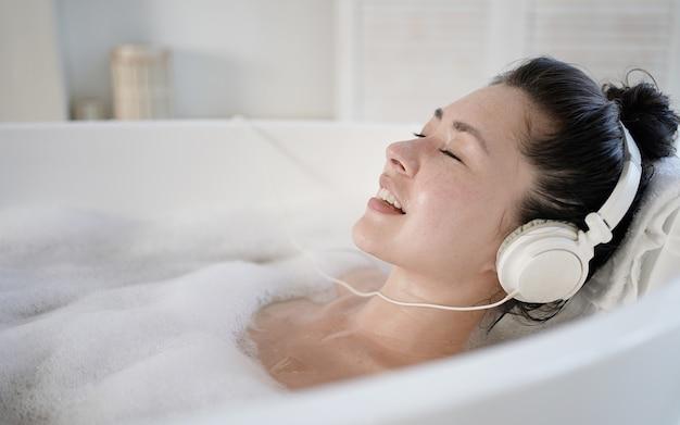 Mulher jovem e atraente asiática com fones de ouvido cantando na banheira com os olhos fechados. garota milenar multiétnica ouvindo música relaxante no banheiro tratamento terapia conceito de estilo de vida saudável