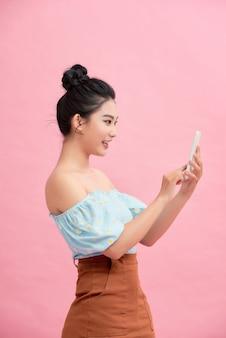Mulher jovem e atraente asiática conversando no aplicativo da web usando tablet ou smartphone, estilo de vida com tecnologia moderna.