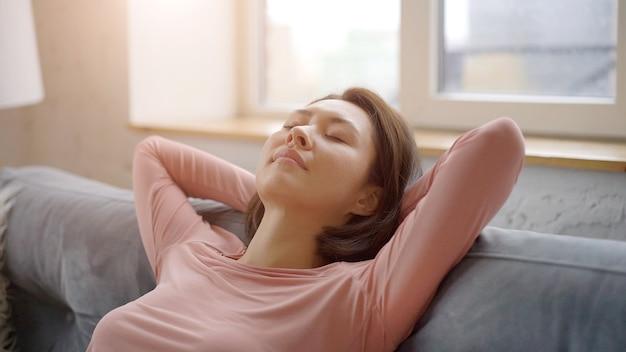 Mulher jovem e atraente asiática descansando em um sofá aconchegante, respirando fundo o ar fresco de mãos dadas atrás da cabeça