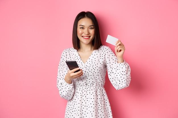 Mulher jovem e atraente asiática pedido on-line, segurando o cartão de crédito e o celular, fazendo compras pela internet, feliz em pé sobre a rosa.