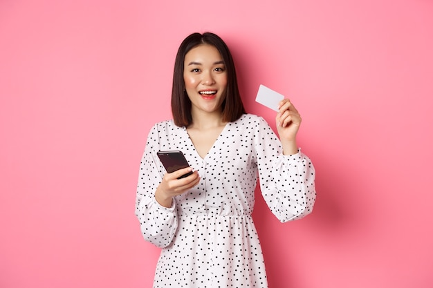 Mulher jovem e atraente asiática pedido on-line segurando o cartão de crédito e o telefone móvel, fazendo compra de internet ...