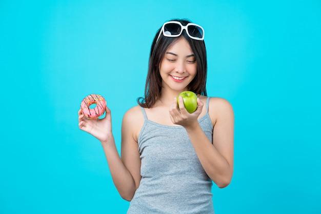Mulher jovem e atraente asiática segurando e escolhendo entre disco de rosquinhas ou fruta maçã verde na parede isolada de cor azul