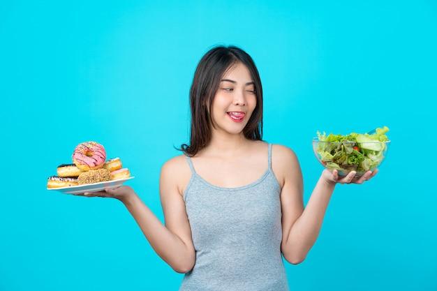 Mulher jovem e atraente asiática segurando e escolhendo entre o disco de donuts ou salada de legumes na tigela de copos