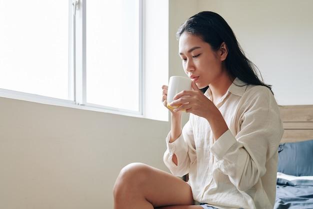 Mulher jovem e atraente asiática sentada na cama desfrutando de uma grande caneca de café saboroso pela manhã