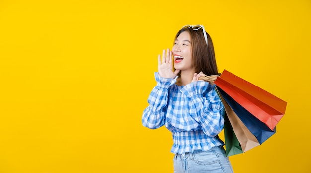 Mulher jovem e atraente asiática sorridente carregando saco coloful de compras na parede amarela aisolated