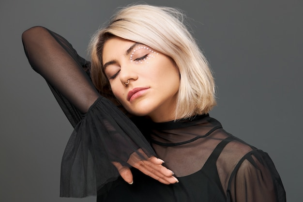 Mulher jovem e atraente atraente com maquiagem artística incrível e corte de cabelo elegante posando com uma blusa preta com reflexos, fechando os olhos e movendo a mão perto do rosto como se estivesse dançando uma música calma