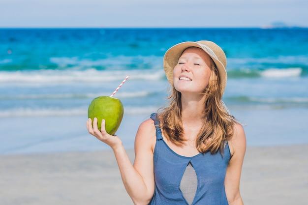 Mulher jovem e atraente bebendo água de coco na praia.
