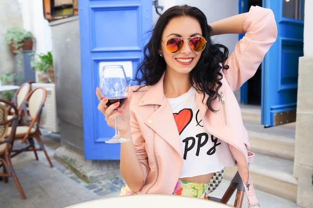 Mulher jovem e atraente bebendo vinho nas férias de verão, sentada em um café de rua da cidade com roupa legal