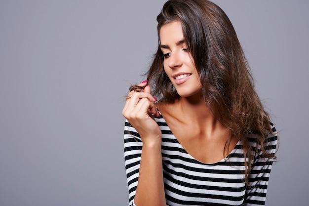 Mulher jovem e atraente brincando com seu cabelo
