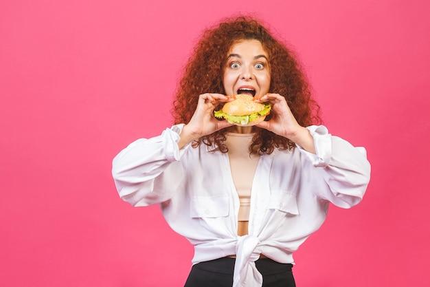 Mulher jovem e atraente caucasiana encaracolada segurando e comendo um hambúrguer grande