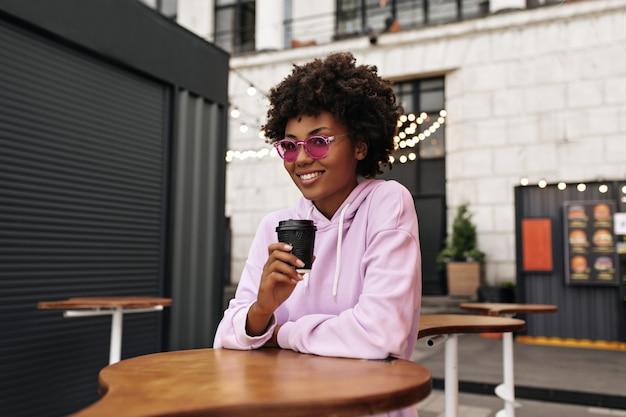 Mulher jovem e atraente charmosa com capuz rosa, óculos de sol coloridos sorri sinceramente, bebe café em um café de rua