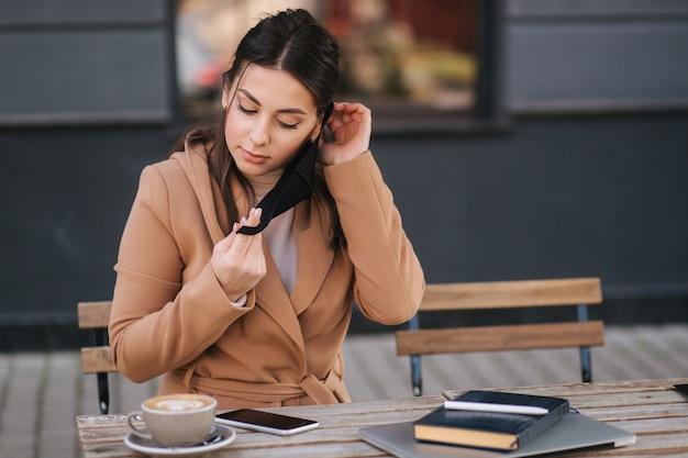 Mulher jovem e atraente colocar máscara protetora preta no terraço perto do café. mulher de casaco marrom sentado e esperando o garçom.