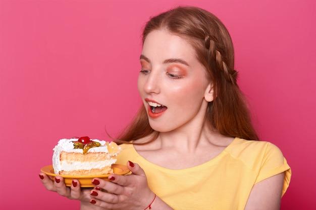Mulher jovem e atraente com a boca aberta mantém o prato com um pedaço de bolo delicioso nas mãos. senhora de cabelos castanho com manicure vermelho