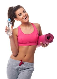 Mulher jovem e atraente com água e esteira para exercícios
