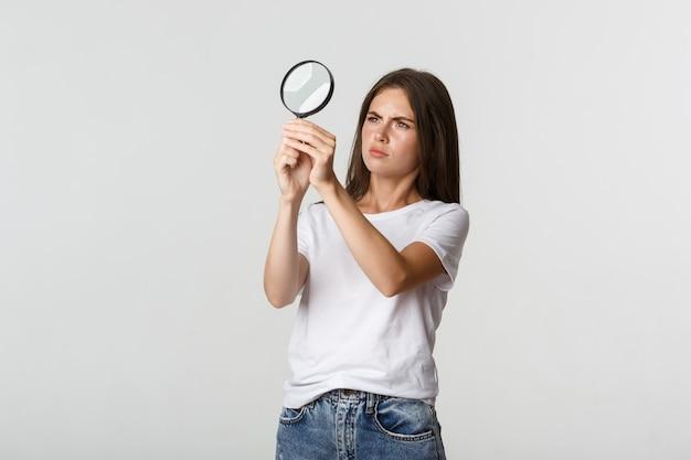Mulher jovem e atraente com aparência séria procurando por algo, olhando através de uma lupa, branca.