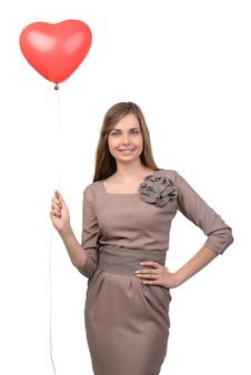 Mulher jovem e atraente com balão em forma de coração.