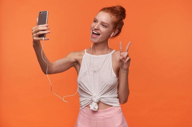 Mulher jovem e atraente com cabeça de leitura com penteado coque usando fones de ouvido, levantando a mão com gesto de paz, olhando para a câmera alegremente enquanto faz selfie com smartphone sobre fundo laranja