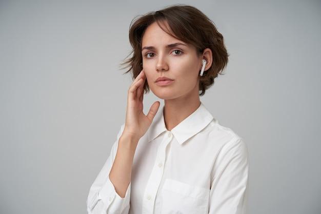 Mulher jovem e atraente com cabelo castanho curto e rosto calmo, tocando seu rosto com a mão levantada em pé