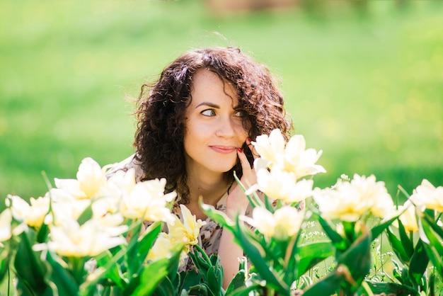 Mulher jovem e atraente com cabelo comprido encaracolado, posando no jardim florido de primavera, macieiras