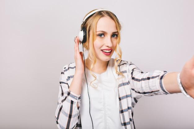 Mulher jovem e atraente com cabelo encaracolado testando o som nos novos fones de ouvido brancos. menina bonita de cabelos louros em roupas elegantes se divertindo e ouvindo música