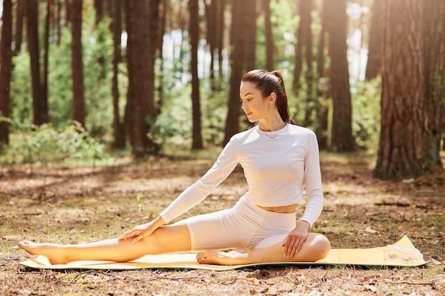 Mulher jovem e atraente com cabelo escuro e rabo de cavalo vestido com roupas esportivas brancas elegantes, sentado no chão na floresta e praticando ioga no karemat