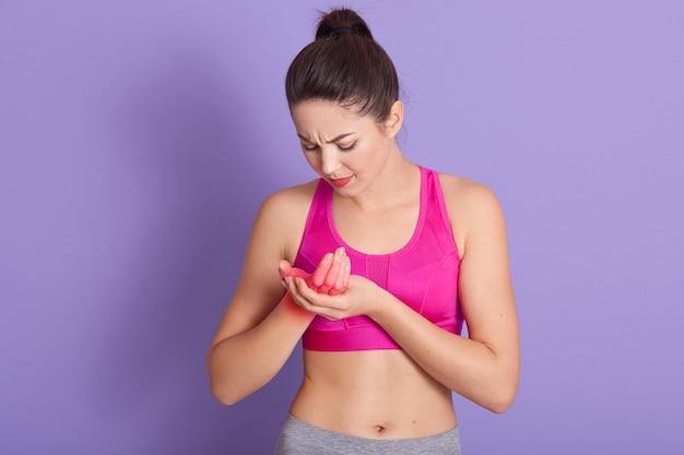 Mulher jovem e atraente com cabelo escuro fere o braço durante o treinamento esportivo, toca na mancha vermelha, indica o local da dor