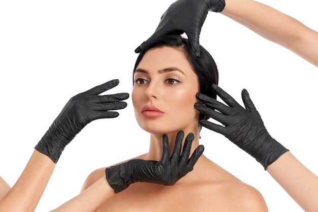 Mulher jovem e atraente com cabelo escuro posando com mãos de esteticista em luvas pretas em volta do rosto
