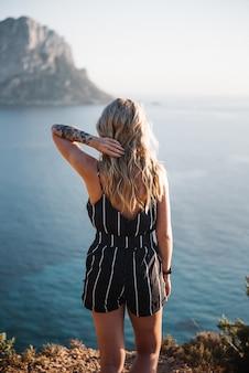 Mulher jovem e atraente com cabelo loiro em pé à beira-mar