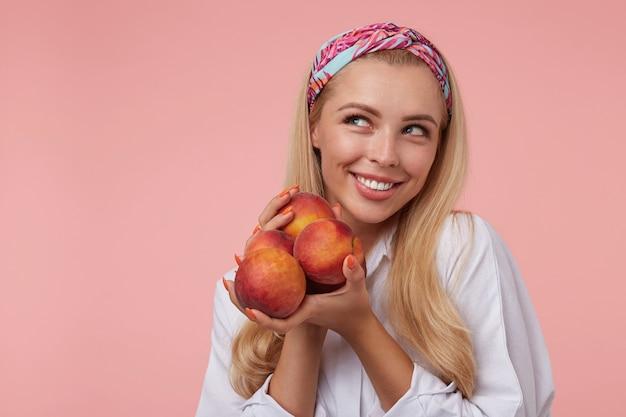 Mulher jovem e atraente com camisa branca e fita colorida com longos cabelos loiros olhando para o lado com alegria, segurando pêssegos nas mãos