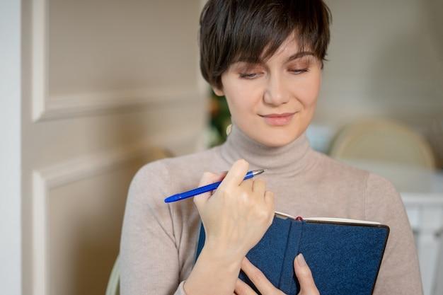 Mulher jovem e atraente com caneta e bloco de notas sorrindo enquanto pensava em novas idéias no café elegante