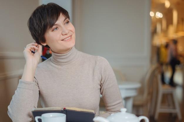 Mulher jovem e atraente com caneta na mão, pensando em planos e escrevendo a lista para fazer no bloco de notas, aproveitando o tempo de recreação no café elegante