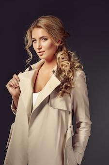 Mulher jovem e atraente com casaco bege, olhando para a câmera