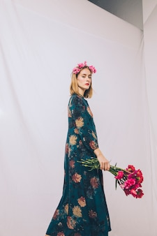 Mulher jovem e atraente com coroa na cabeça e ramo de flores