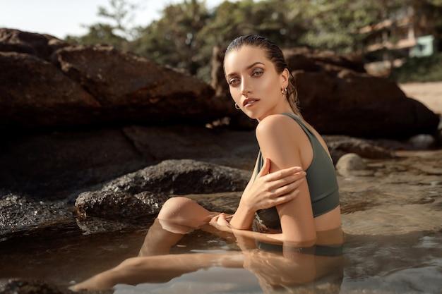 Mulher jovem e atraente com corpo perfeito e bronzeado posando na praia
